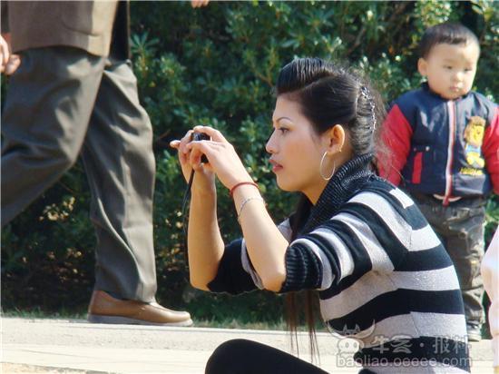 公园里一美女拍照很专致