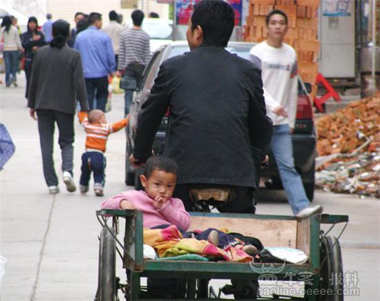 一个小孩子坐在大人的脚踏车里
